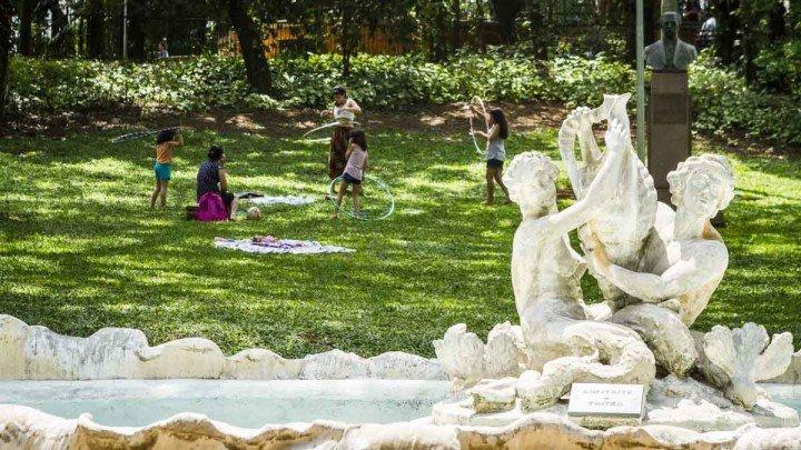 Foto de estátua com crianças brincando no gramado, ao fundo. Cena do Parque Buenos AIres, um lugar para ver e viver em São Paulo, fotografado pelo Rodolfo Goud para o guia Viajo.City